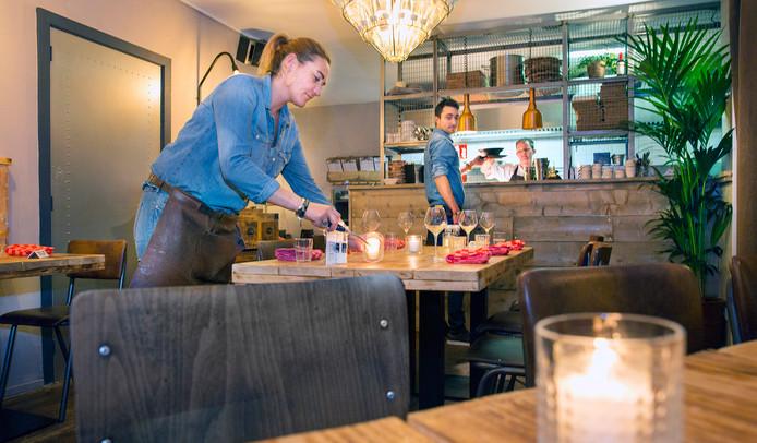 Eigenaar Marieke von Holtz ontsteekt de kaarsjes, in het midden mede-eigenaar Milan van Melsen bij de open keuken.