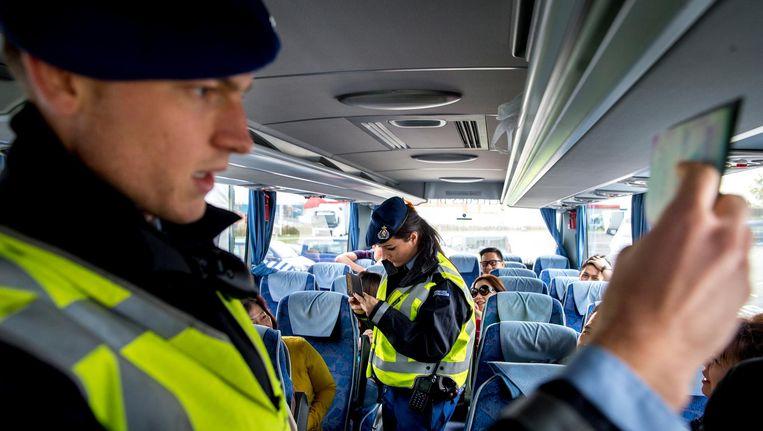 Medewerkers van de Koninklijke Marechaussee voeren een controle uit in een bus. Beeld anp