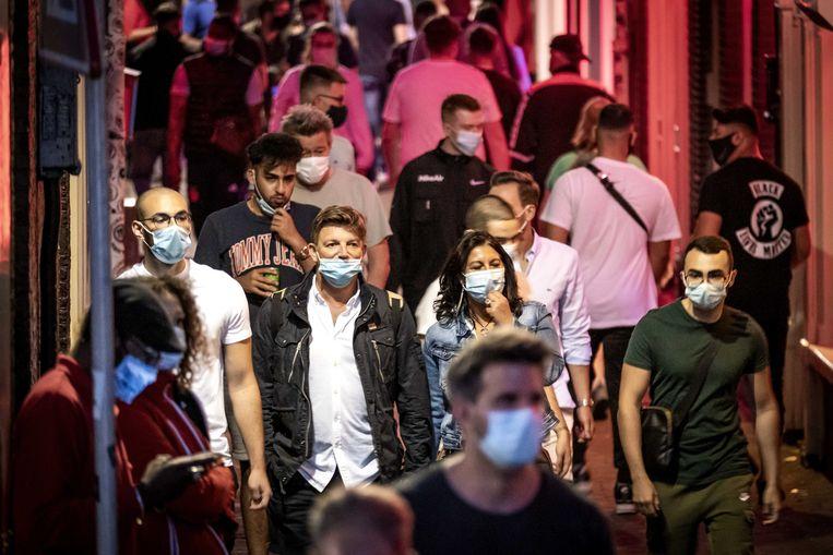 Bezoekers op de Amsterdamse Wallen. Amsterdam, Rotterdam en Den Haag kleuren rood op de besmettingskaarten en het kabinet eist zichtbare actie.  Beeld ANP