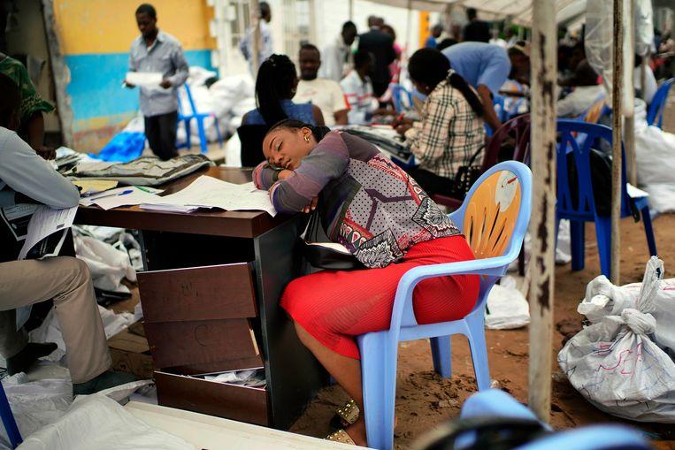 Een uitgeput lid van de kiescommissie neemt rust tijdens het tellen van de stemmen in Congo. Beeld AP