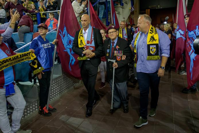 Stef ten Thij van de Supportersvereniging Vitesse leidt een oorlogsveteraan stadion GelreDome binnen voor de jaarlijkse Airborne-wedstrijd.