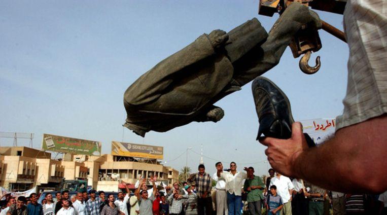 Het beeld van Saddam gaat van zijn sokkel. © EPA Beeld