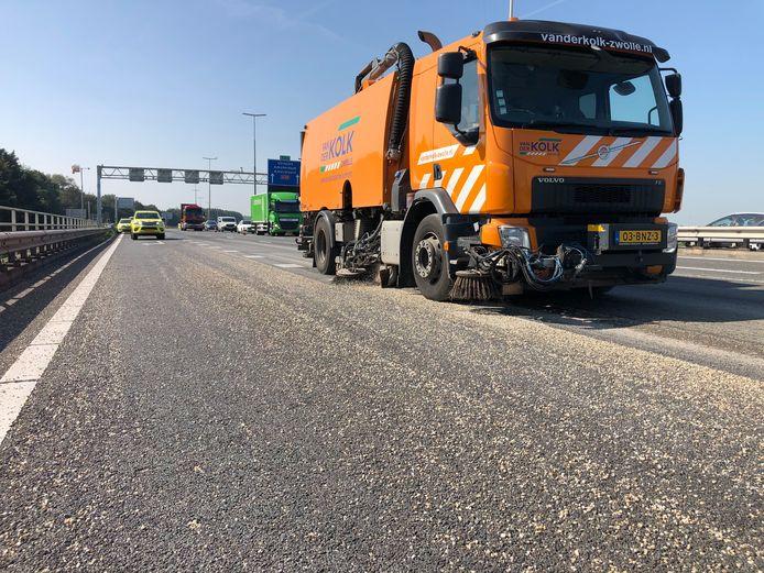 De A28 ligt bezaaid met grind. Rijkswaterstaat is met ZOAB-veegwagens bezig de kleine steentjes van het wegdek te krijgen.