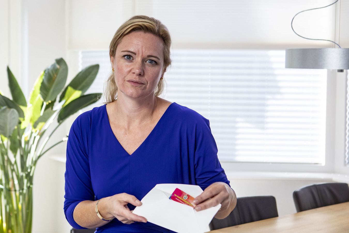 """Evelien Morriën schuift symbolisch haar ledenpas in een envelop. """"Mocht de deur voor vrouwen geopend worden dan meld ik mij direct weer aan als lid."""""""
