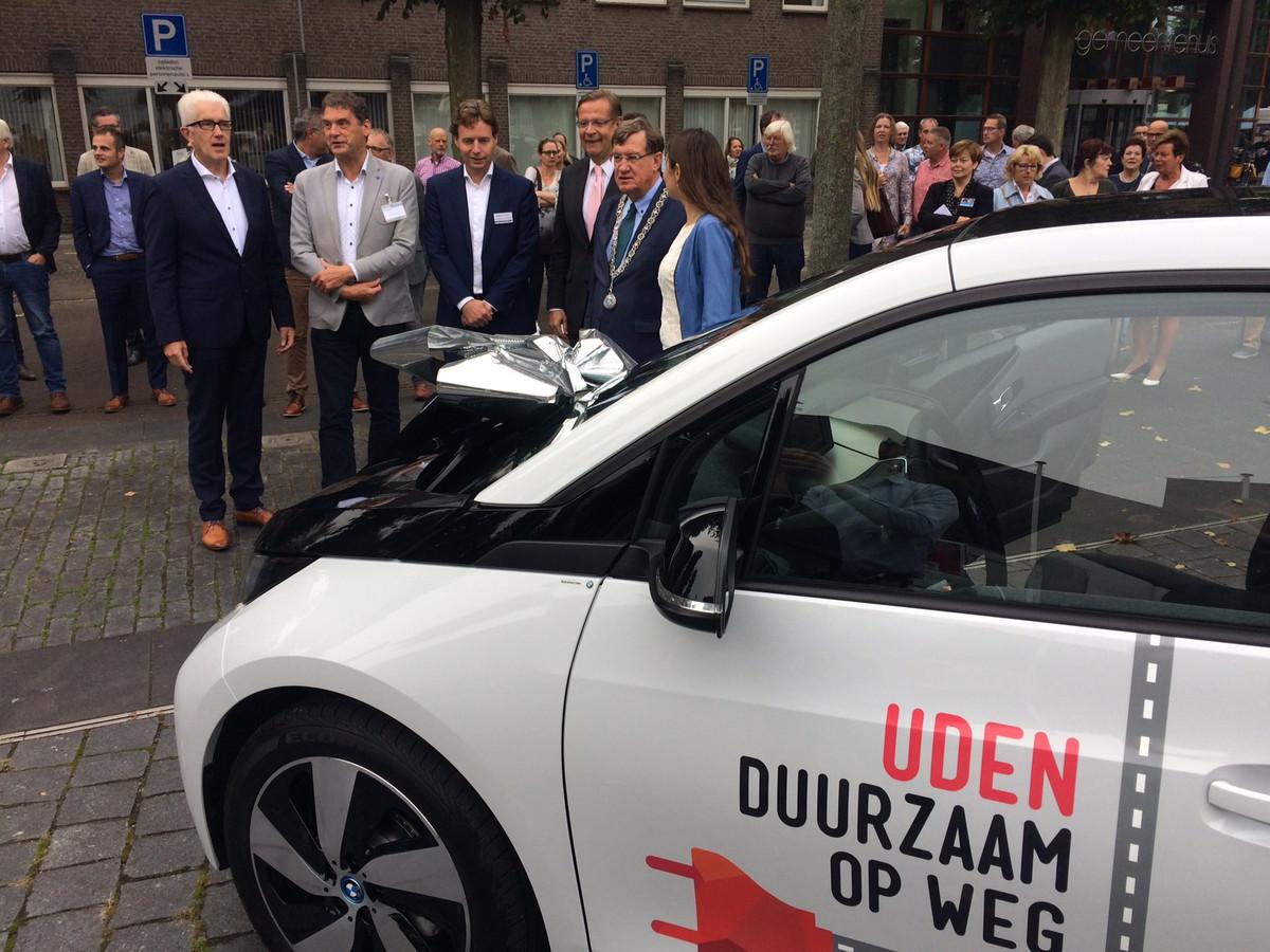 De drie trotse partijen bij een van de veertien elektrische BMW's die in Uden en omstreken gaan rijden. Vlnr Matthie van Merwerode, Jan van Vucht (Area), Maarten Gielen (IBN), Jeroen Smarius, burgemeester Henk Hellegers, gedeputeerde Anne-Marie Spierings.