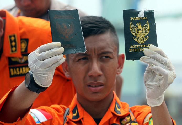 Reddingwerkers tonen gevonden voorwerpen, waaronder paspoorten van passagiers van vlucht JT61-0