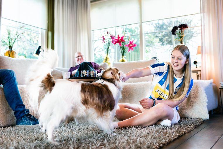 Fleur Harshagen (18) thuis bij haar vader (links buiten beeld) in het Nederlandse Lienden, met haar opa op de bank. Al vijftien jaar verplaatst Fleur zich tweemaal per week tussen de huizen van haar co-ouderende vader en moeder.
