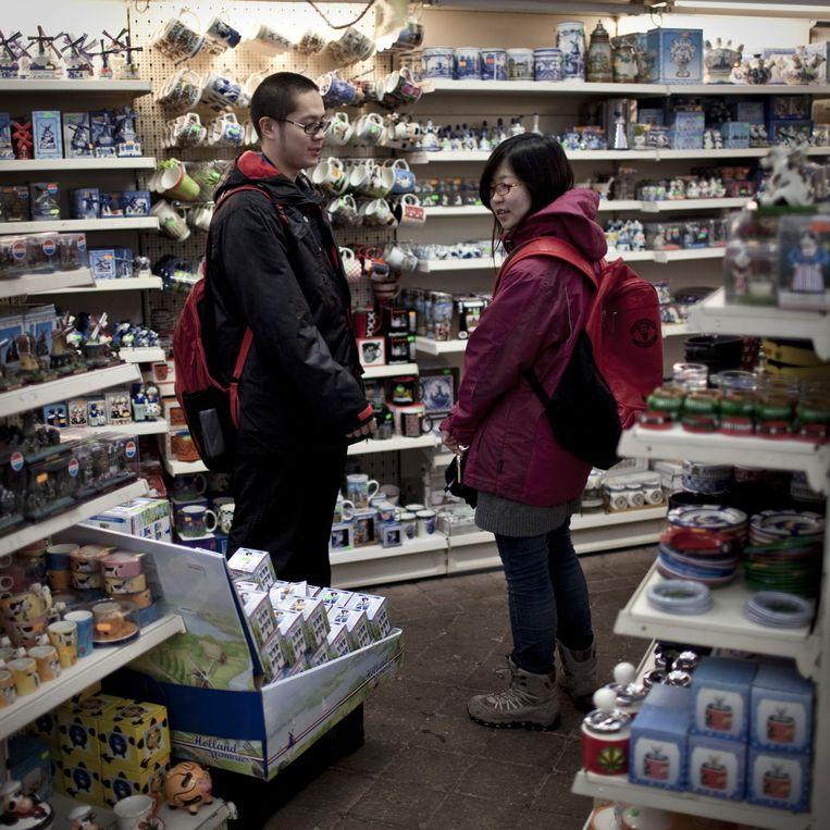 Aziatische toeristen in een souvenirwinkel op de bloemenmarkt in Amsterdam. Beeld Julius Schrank