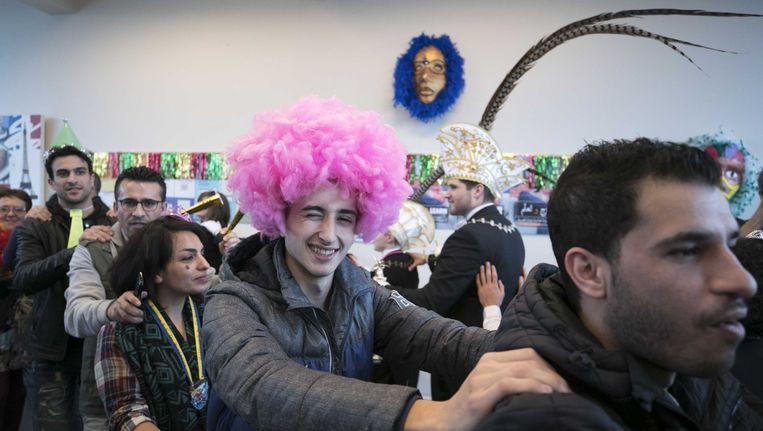 Tijdens een inburgeringscursus voor immigranten geven leden van de carnavalsvereniging Winkbulle in Heerlen een gastles. Beeld anp