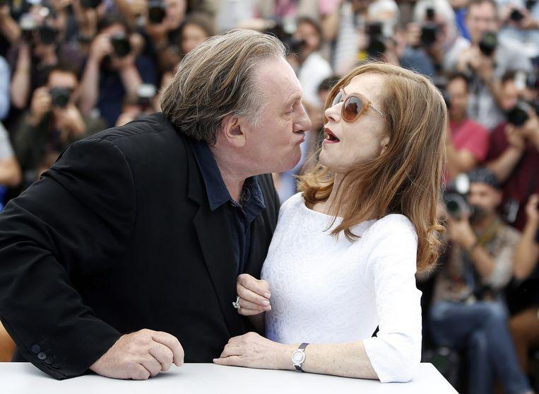 De Franse acteur Gerard Depardieu (L) probeert de Franse actrice Isabelle Huppert te zoenen tijdens het Film Festival in Cannes. Beeld epa