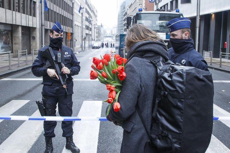 De marechaussee laat een vrouw door die bloemen wil leggen bij de plek van de aanslag, bij metrostation Maalbeek. Beeld belga