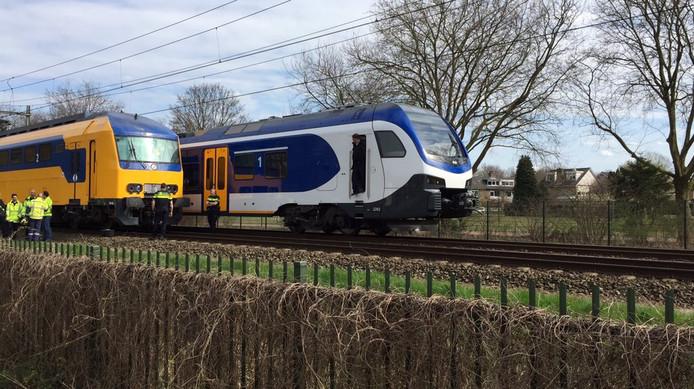 Passagiers van de vanwege een aanrijding gestrande trein bij Rosmalen stappen over in een andere.