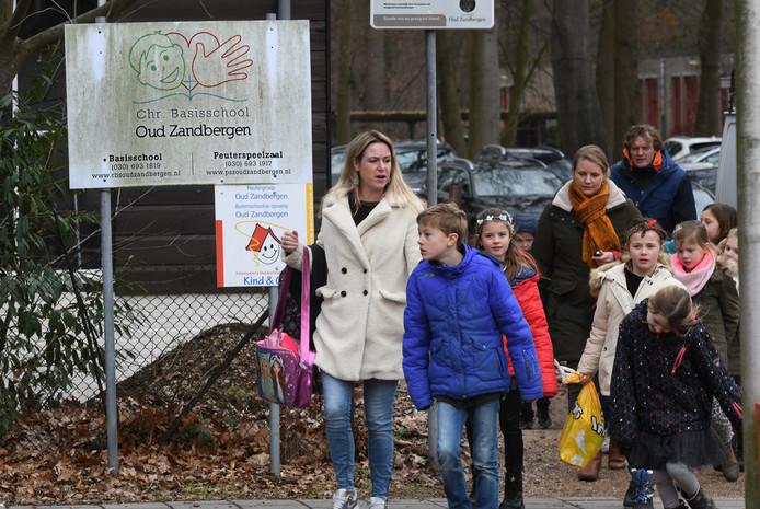 Ouders verlaten met hun kinderen het terrein  van de basisschool Oud Zandbergen in Huis ter Heide .