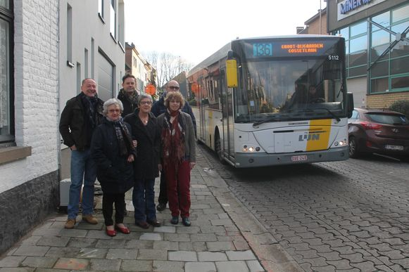De leden van het buurtcomité in de Spanjebergstraat, terwijl een bus richting centrum rijdt. Die rijrichting willen ze geschrapt zien.
