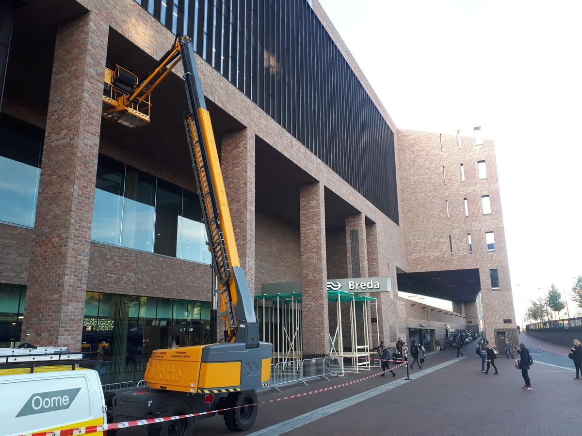 Onderzoek met hoogwerker aan station Breda naar aanleiding van vallende stenen. Op de achtergrond de houten overkapping voor de ingang.