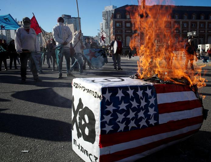 Demonstranten verbranden een Amerikaanse vlag voor het gebouw waar de G20-handelsministers bijeen zijn. Ze protesteren tegen het Amerikaanse economische beleid en dat van de Argentijnse president Macri, die kampt met een ernstige economische en financiële crisis in het land.