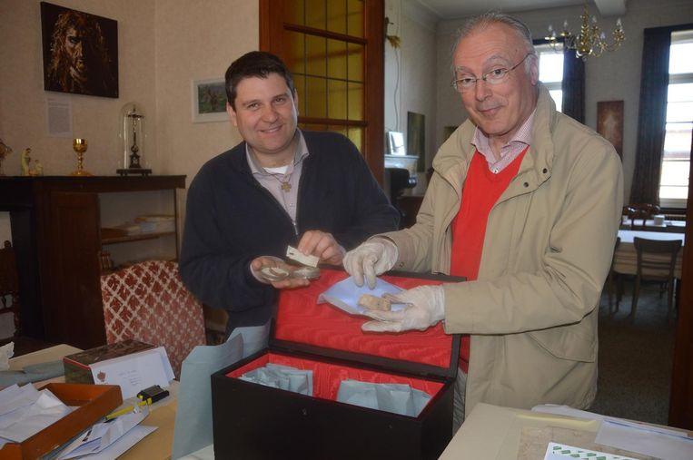 Pastoor Alexander Vandaele en historicus Jaak Peersman tonen enkele relikwieën uit de kist.