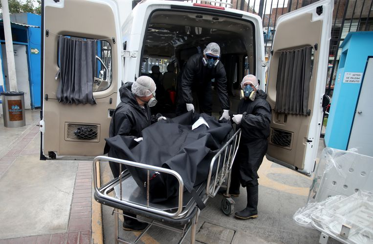 Het lichaam van een overleden coronapatiënt wordt opgehaald uit een ziekenhuis in Lima, Peru.  Beeld Getty Images