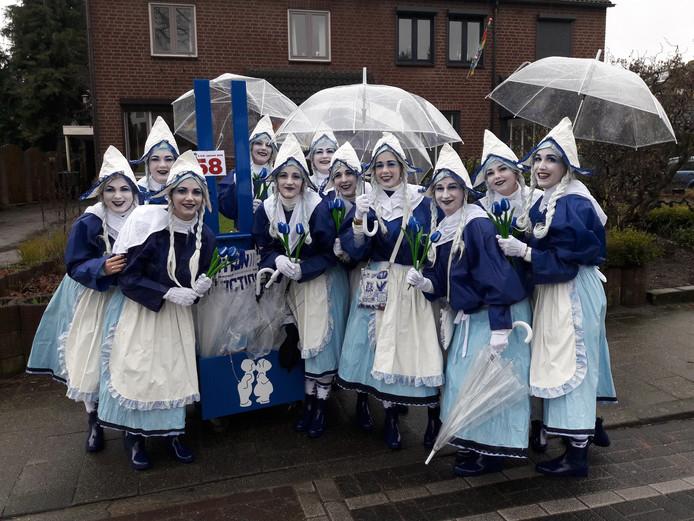 De vrouwen van carnavalsvereniging Now Da Wer op weg in de optocht, met paraplu's.
