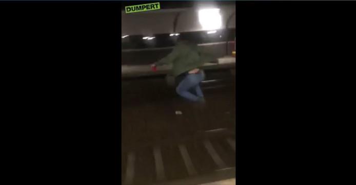 De jongeman springt van het perron vlak voor een trein het spoor op.