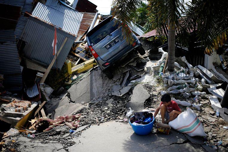 Een jongetje zit voor zijn verwoeste huis in Palu. Beeld AP