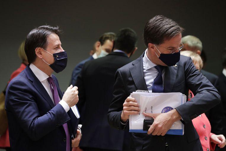 Premier Mark Rutte (rechts) wendt het hoofd af als hij even moet hoesten terwijl hij in gesprek is met zijn Italiaanse ambtsgenoot Giuseppe Conte op de eerste dag van de EU-top in Brussel.  Beeld AP