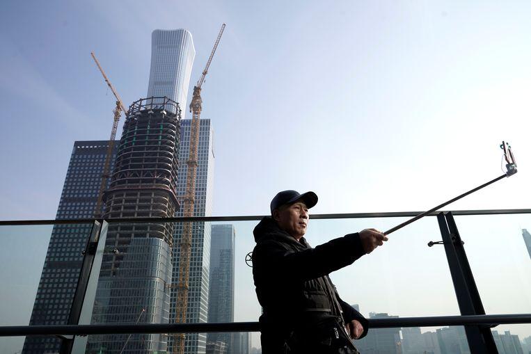 Een man neemt een selfie in het zakencentrum van Beijing.   Beeld Reuters