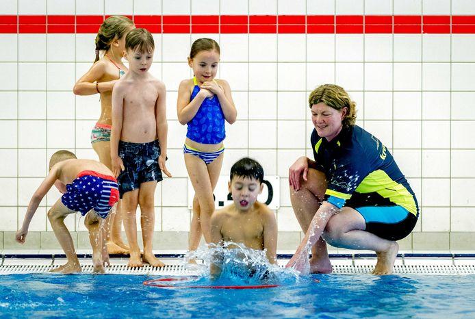 Een docent geeft aanwijzingen tijdens een zwemles voor kinderen in een zwembad voor het behalen van de Nationale Zwemdiploma.