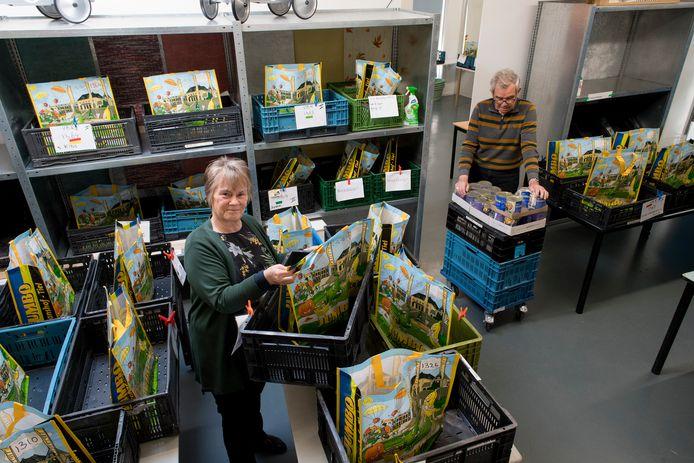Joke Steigerwald tussen de tassen met etenswaren die in kratten worden klaar gezet. Om de kans op coronabesmetting zo klein mogelijk te houden, mogen klanten van Voedselbank Rivierenland niet meer zelf winkelen.