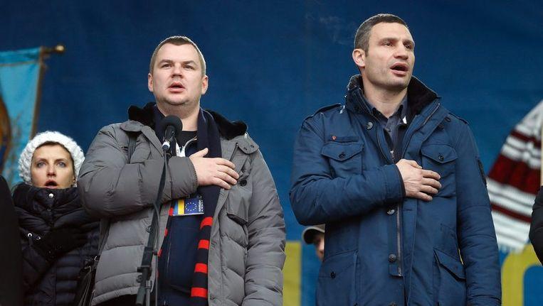 De Oekraïense antiregeringsdemonstrant Dmitri Boelatov en oppositieleider Vitali Klitsjko (R) zingen het volkslied tijdens een demonstratie in Kiev. Beeld epa