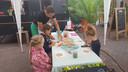 Pieter helpt de kids bij de workshop pizza bakken