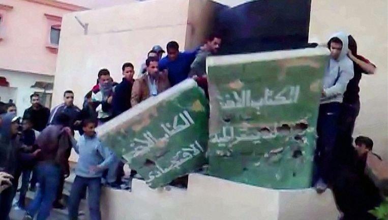 Woedende betogers vernietigen het groene boekje van Khadaffi. Screenshot van ongedateerde video. Beeld afp