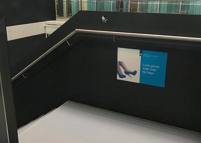 De gewraakte poster waarop vrouwenbenen op hoge hakken te zien zijn, met daarbij de tekst 'Loop gerust weer over mij heen'.