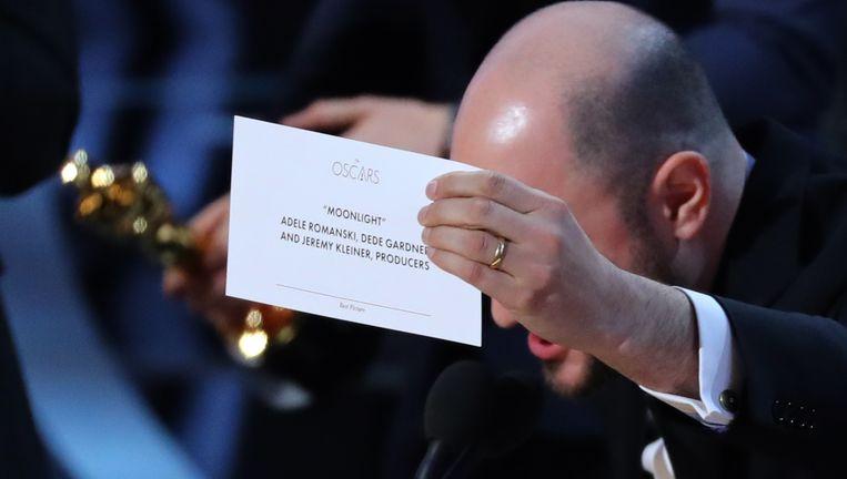 De producent van de show houdt een kaartje omhoog met de juiste winnaar. Beeld REUTERS