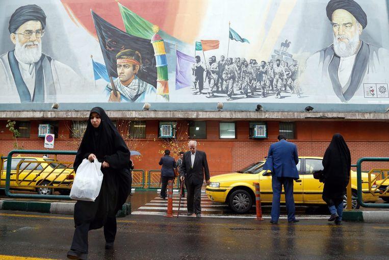 Mensen op straat in Teheran. Op de achtergrond levensgrote portretten van ayatollah Khamenei en de voormalige ayatollah Ruhollah Khomeini. Beeld EPA