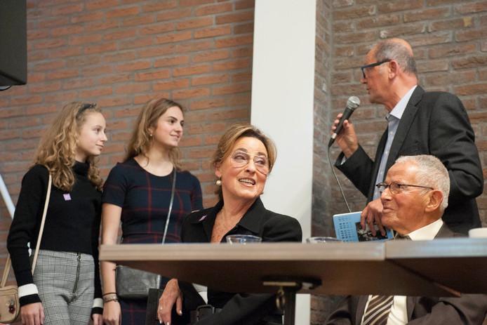 Kleinkinderen Noa en Stella krijgen bij de boekpresentatie in Maastricht uit handen van schrijver Frans Hermans een boek over de oorlogservaringen van hun opa. Hijman Gans en zijn vrouw Ellen kijken trots toe.