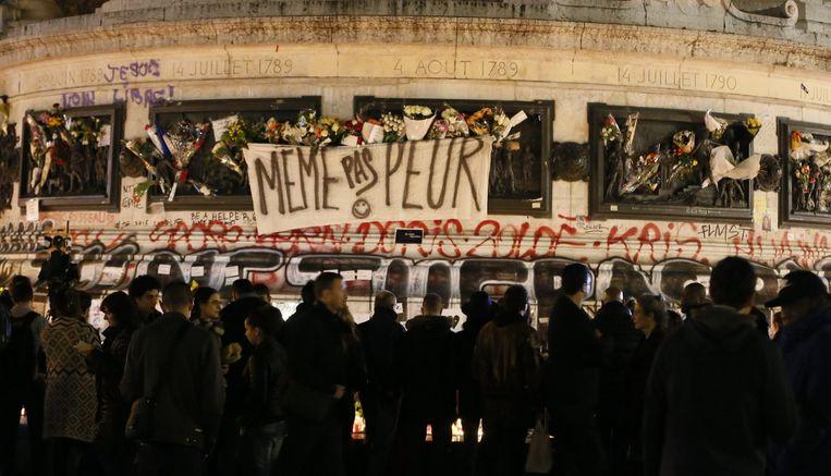 Place de la Republique, vlakbij enkele van de locaties waar de aanslagen vrijdag plaatsvonden, is dezer dagen een plaats van herdenking. 'Totaal niet bang', staat er (vrij vertaald) op het spandoek. Beeld epa