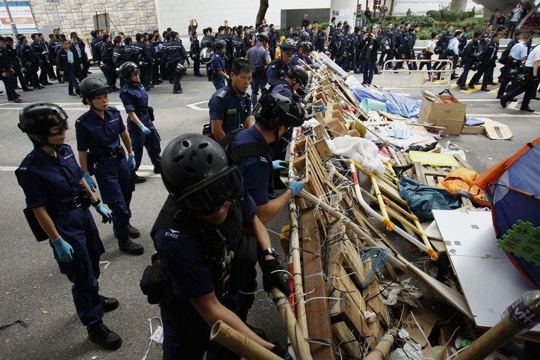 Politieagenten breken een barricade van de demonstranten af. Beeld reuters