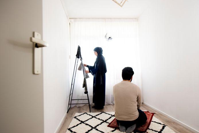 Sebnem Asilsoy-Yozgat haalt een gebedskleedje van het rek in de ruimte die ze thuis speciaal hebben ingericht om te bidden. Rechts haar man Muhammed.