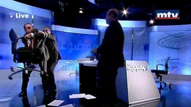 Shukr (links) wil een stoel gooien naar Alloush. De talkshowhost moet hem tegenhouden. Beeld AFP