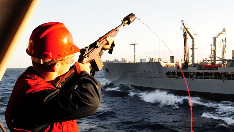 Een opvarende van het Amerikaanse marineschip USS George Washington schiet een lijn naar het oliebevoorradingsschip USNS Tippecanoe bij een eerdere gemeenschappelijke oefening van de Verenigde Staten en Zuid-Korea. Beeld AFP