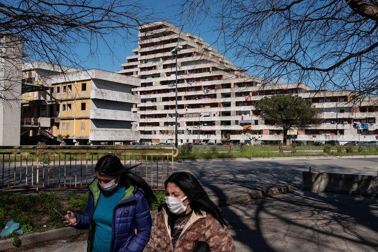 Twee vrouwen lopen voorbij het populaire woningproject Le Vele di Scampia in Napels, Italië. Beeld Giulio Piscitelli