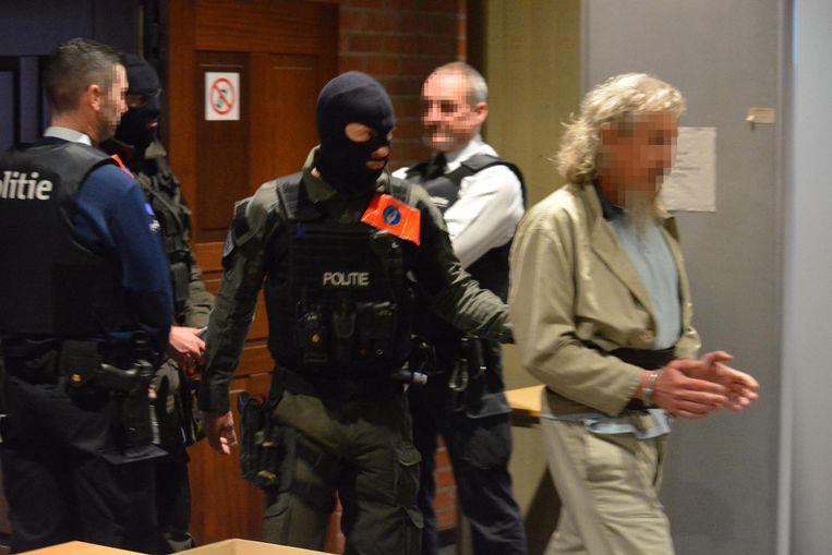 Chalil M., de vermeende leider, wordt door de speciale interventie-eenheid naar de rechtszaal gebracht.