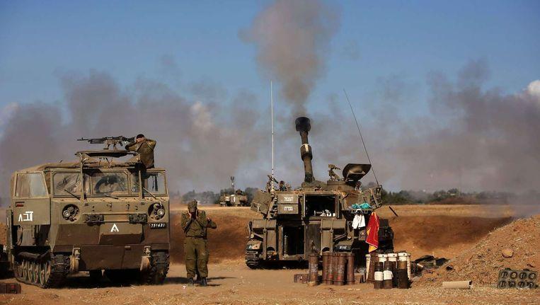 Een Israëlische tank schiet een raket richting de Gazastrook. Beeld afp