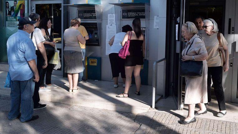 Grieken in de rij bij een geldautomaat in Athene. Beeld afp