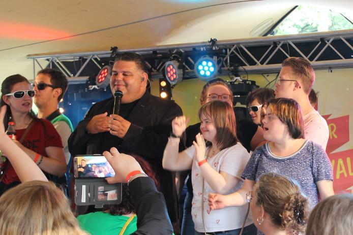 Django Wagner wordt omringd door publiek dat gepassioneerd meezingt.