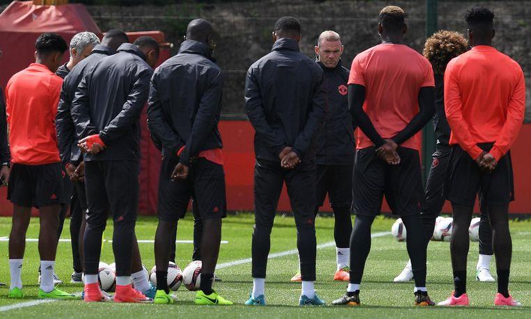 De spelers van Manchester United houden een minuut stilte voor hun training. Beeld anp