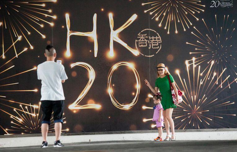 Een jong gezin bij een affiche waarop de 20ste verjaardag van de overdracht wordt gevierd. Beeld epa