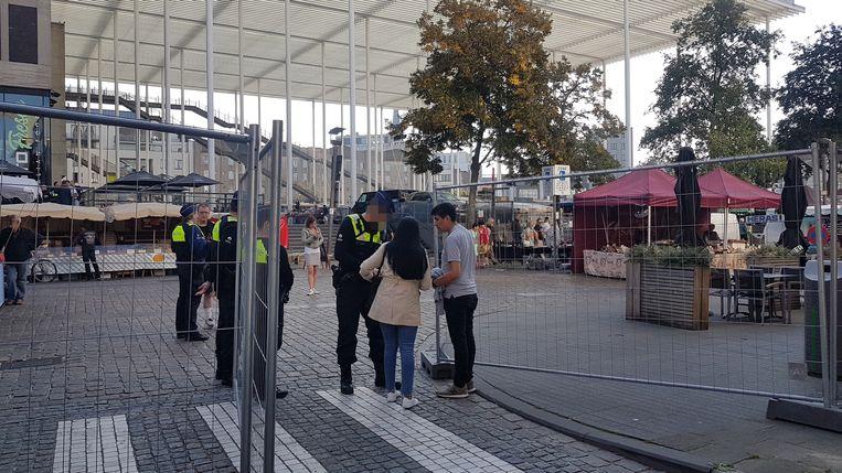 Een agent doorzoekt een handtas van marktbezoekers.