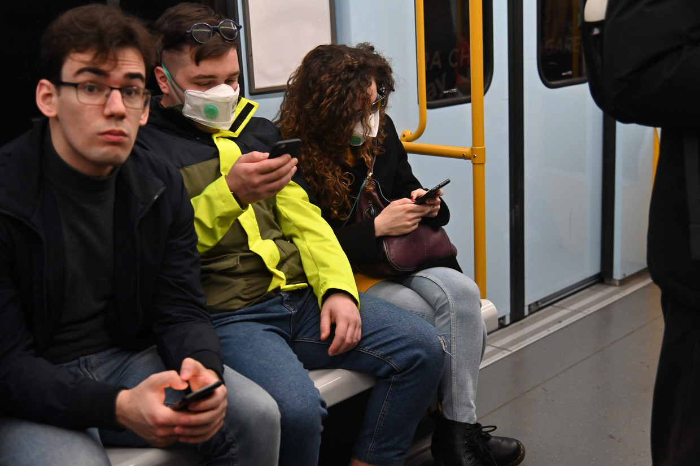 In de metro van Milaan dragen veel mensen mondkapjes en maskers om besmetting tegen te gaan. Beeld AFP